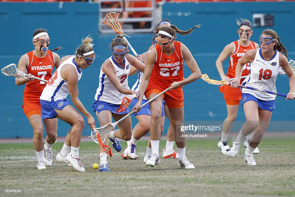 Kelly Cross #27 of the Syracuse Orange fights for control of the ball with Emily Dohony #2 and Kayla Stolins #20 of the Florida Gators during the 2013 Orange Bowl Lacrosse Classic on March 2, 2013 at SunLife Stadium in Miami Gardens, Florida.