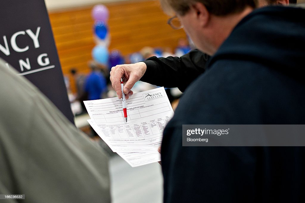 Kelly Davis, regional manager for The Agency Staffing, points out the skills section on an application as he talks with a job seeker during a job fair at Illinois Valley Community College (IVCC) in Oglesby, Illinois, U.S., on Wednesday, April 10, 2013. The U.S. Department of Labor is scheduled to release jobless claims figures on April 11. Photographer: Daniel Acker/Bloomberg via Getty Images