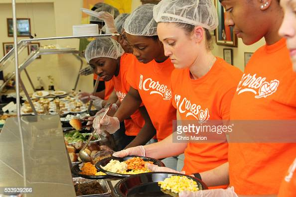 Kelly Faris of the Connecticut Sun particiate at a WNBA Cares event and serves food at the New London Community Meal Center on May 23 2016 in New...