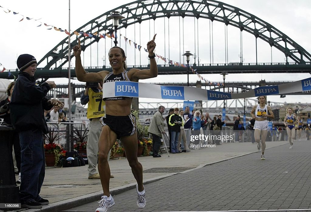 Kelly Holmes of Great Britain crosses the line to win the women's BUPA Great North Mile on Newcastle Quayside, Newcastle, England on October 05, 2002. (Photo by Bryn Lennon/Getty Images).
