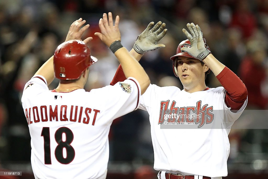 Kelly Johnson #2 of the Arizona Diamondbacks high-fives teammate Willie Bloomquist #18 after Johnson hit a 3 run home run against the Cincinnati Reds during the eighth inning of the Major League Baseball home opening game at Chase Field on April 8, 2011 in Phoenix, Arizona.