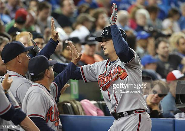 Kelly Johnson of the Atlanta Braves is congratulated by manager Fredi Gonzalez and bench coach Carlos Tosca in the dugout after hitting a tying solo...