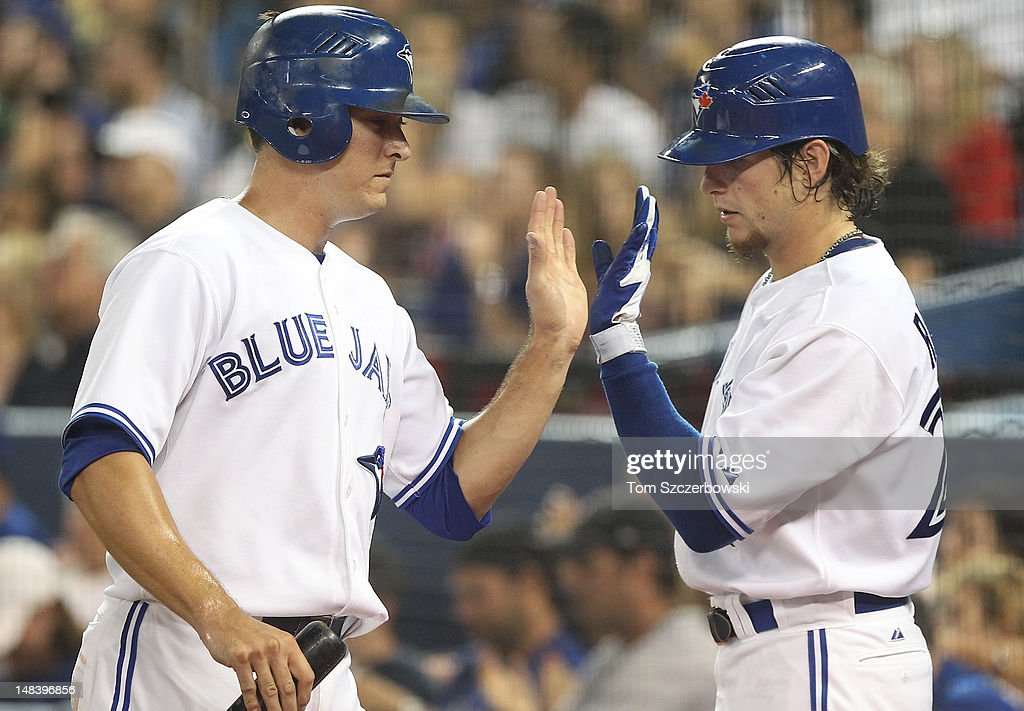 Kelly Johnson #2 of the Toronto Blue Jays is congratulated by <a gi-track='captionPersonalityLinkClicked' href=/galleries/search?phrase=Colby+Rasmus&family=editorial&specificpeople=3988372 ng-click='$event.stopPropagation()'>Colby Rasmus</a> #28 after scoring a run in the 3rd inning during MLB game action against the Cleveland Indians on July 15, 2012 at Rogers Centre in Toronto, Ontario, Canada.