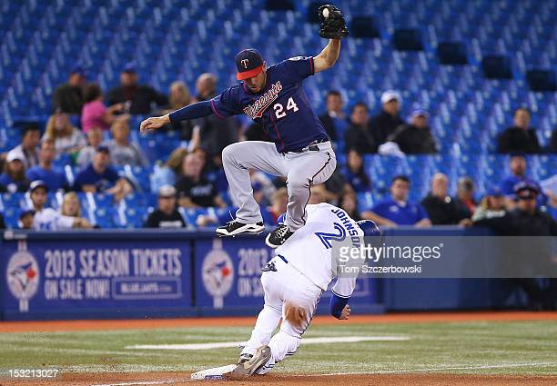 Kelly Johnson of the Toronto Blue Jays steals third base in the eighth inning during MLB game action as Trevor Plouffe of the Minnesota Twins catches...