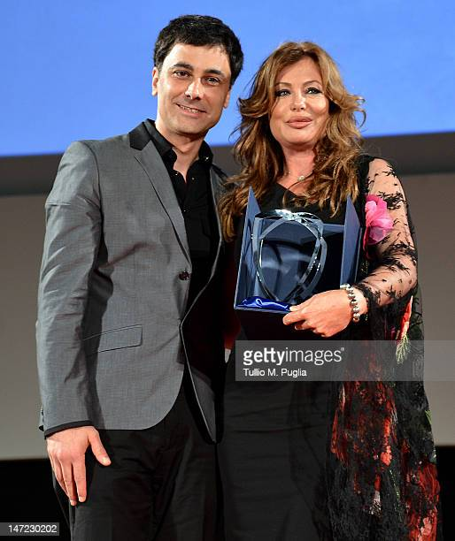 Kelly LeBrock receives the Lancia Award from Saad Chehab CEO of ChryslerLancia during the 58th Taormina Film Fest on June 27 2012 in Taormina Italy