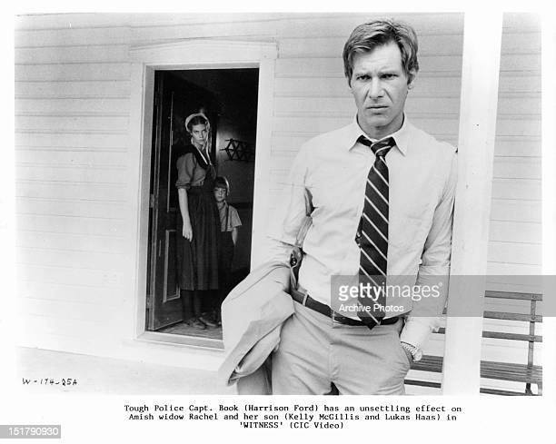 Kelly McGillis Lukas Haas and Harrison Ford stand by a white house in a scene from the film 'Witness' 1985