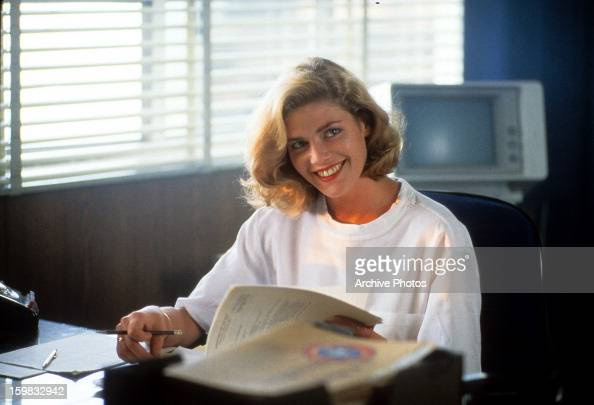 Kelly McGillis sits at a desk in a scene from the film 'Top Gun' 1986