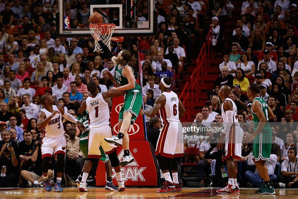 Kelly Olynyk #41 of the Boston Celtics attempts a shot as Chris Bosh #1 of the Miami Heat and Dwyane Wade #3 of the Miami Heat look on at American Airlines Arena on November 9, 2013 in Miami, Florida.