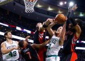 Kelly Olynyk of the Boston Celtics attempts to grab a loose rebound in front of Terrence Ross and Kyle Lowry of the Toronto Raptors in the second...
