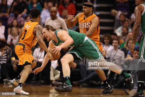 Kelly Olynyk of the Boston Celtics drives the ball past Tyler Ulis and Jared Dudley of the Phoenix Suns during the first half of the NBA game at...