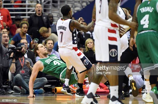 Kelly Olynyk of the Boston Celtics is knocked to the floor by Kelly Oubre Jr #12 of the Washington Wizards in the second quarter during Game Three of...