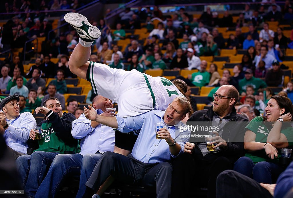 Kelly Olynyk #41 of the Boston Celtics runs over the first row of fans in their seats in the second half against the Washington Wizards during the game at TD Garden on April 16, 2014 in Boston, Massachusetts.