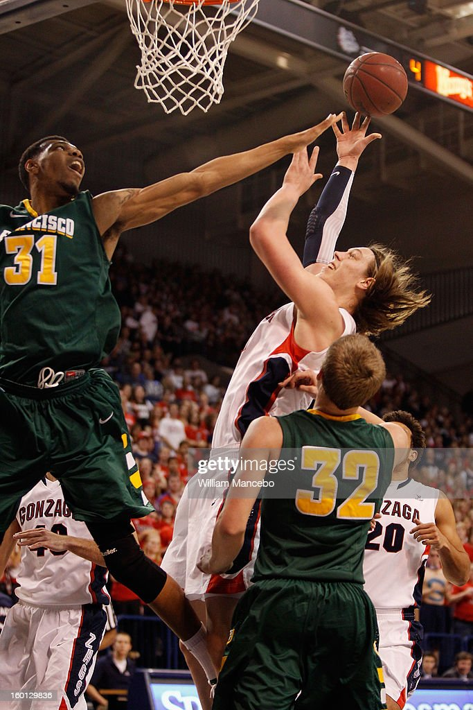 Kelly Olynyk #13 of the Gonzaga Bulldogs attempts to score a goal against forward Frank Rogers #31 and guard Tim Derksen #32 of the San Francisco Dons during the game at McCarthey Athletic Center on January 26, 2013 in Spokane, Washington.