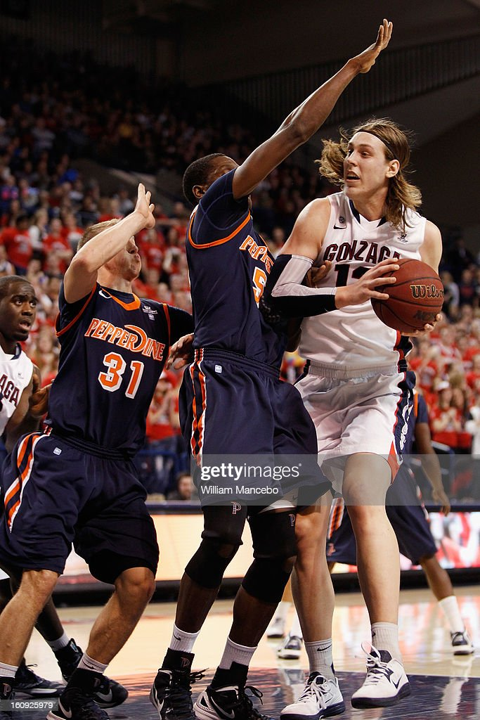 Kelly Olynyk #13 of the Gonzaga Bulldogs controls the ball while forward Stacy Davis #5 and guard Nikolas Skouen #31 of the Pepperdine Waves defend during the first half of the game at McCarthey Athletic Center on February 7, 2013 in Spokane, Washington.