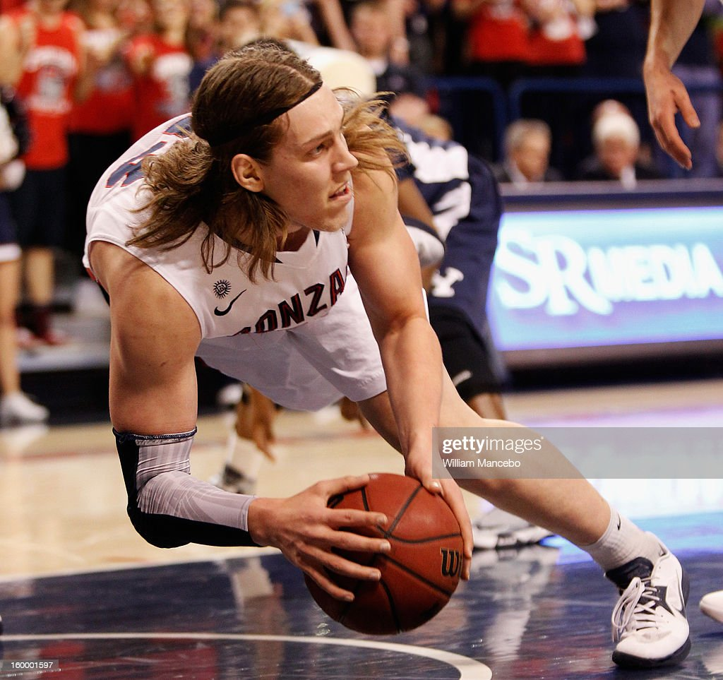 Kelly Olynyk #13 of the Gonzaga Bulldogs looks to pass the ball as he falls to the floor during the first half of the game against the BYU Cougars at McCarthey Athletic Center on January 24, 2013 in Spokane, Washington.