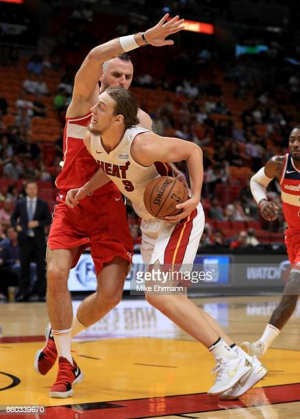 Kelly Olynyk of the Miami Heat drives on Marcin Gortat of the Washington Wizards during a preseason game at American Airlines Arena on October 11...