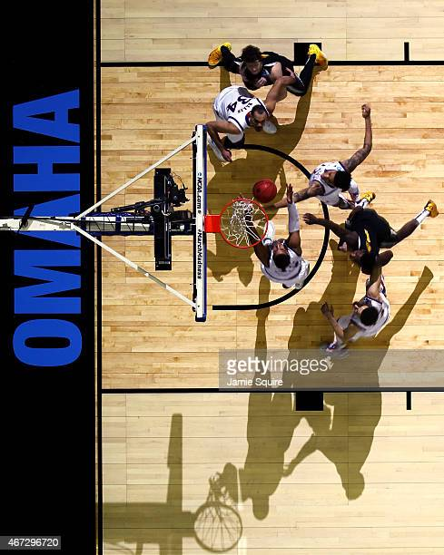 Kelly Oubre Jr #12 and Landen Lucas of the Kansas Jayhawks jump for a rebound during the third round game of the NCAA Basketball Tournament against...