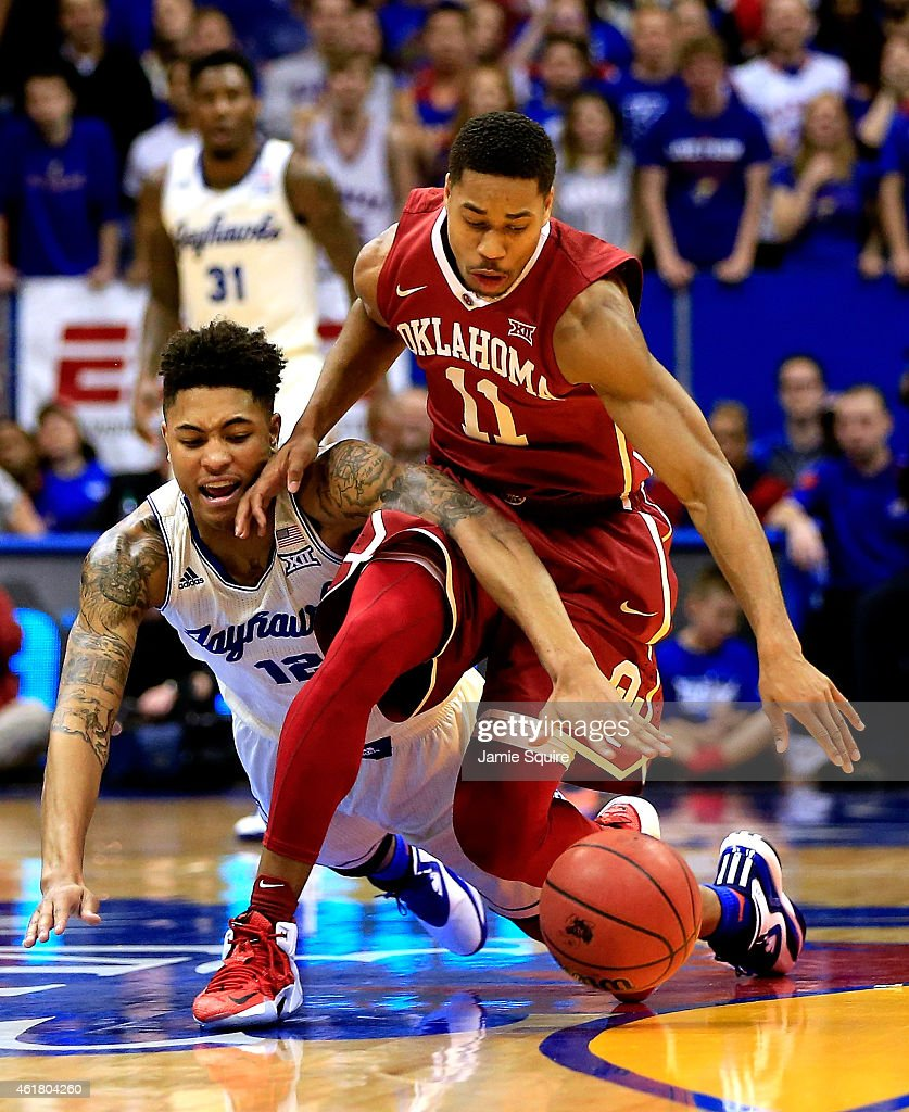 Kelly Oubre Jr #12 of the Kansas Jayhawks battles Isaiah Cousins of the Oklahoma Sooners for a loose ball during the game at Allen Fieldhouse on...