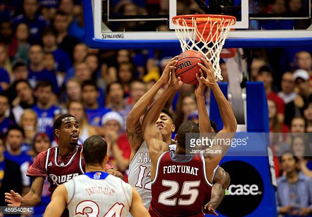 Kelly Oubre Jr #12 of the Kansas Jayhawks blocks a shot by Junior Fortunat of the Rider Broncs during the game at Allen Fieldhouse on November 24...