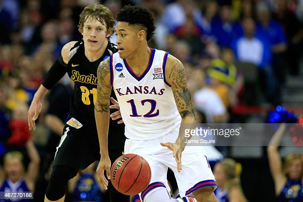 Kelly Oubre Jr #12 of the Kansas Jayhawks dribbles past Ron Baker of the Wichita State Shockers in the first half during the third round of the 2015...