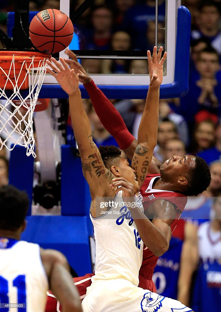 Kelly Oubre Jr #12 of the Kansas Jayhawks fouls Buddy Hield of the Oklahoma Sooners during the game at Allen Fieldhouse on January 19 2015 in...
