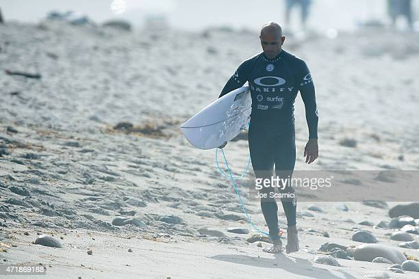 Kelly Slater of the US comes onto shore after moving forward to the next round in the round of 24 during the Oakley Lower's Pro at Lower Trestles on...