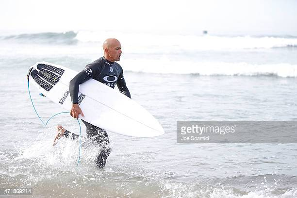 Kelly Slater of the US runs back to the water after a board change in the round of 24 during the Oakley Lower's Pro at Lower Trestles on May 1 2015...