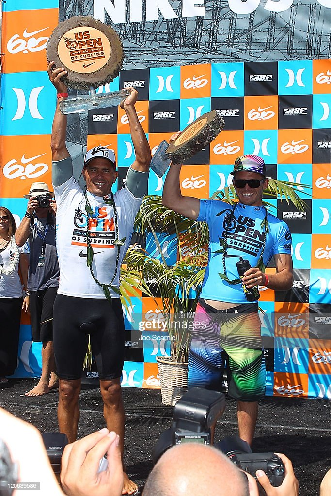 Kelly Slater of USA and Yadin Nicols of Australia on the winners podium holding their trophys at the Nike US Open of Surfing on August 7 2011 in...
