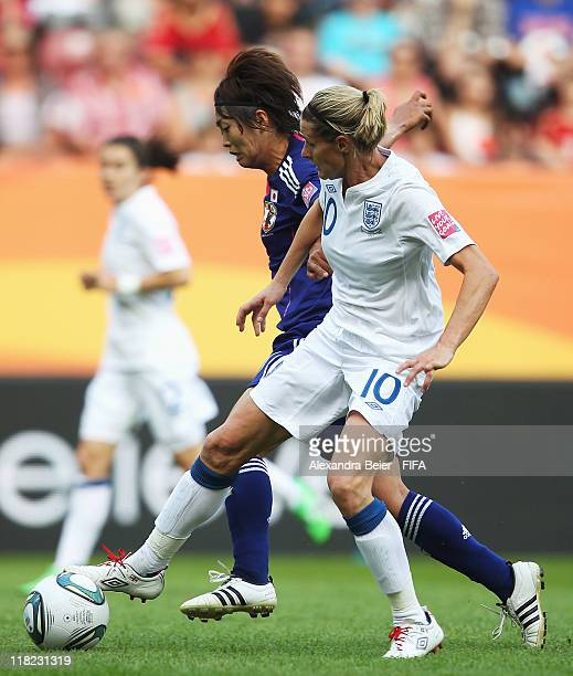 Kelly Smith of England fights for the ball with Kozue Ando of Japan during the FIFA Women's World Cup 2011 group B match between England and Japan at...