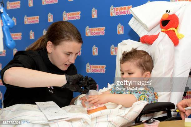 Kelly Therrien of Dunkin' Donuts shows Isaak how to make a donut during Iced Coffee Day benefitting Boston Children's Hospital at Boston Children's...