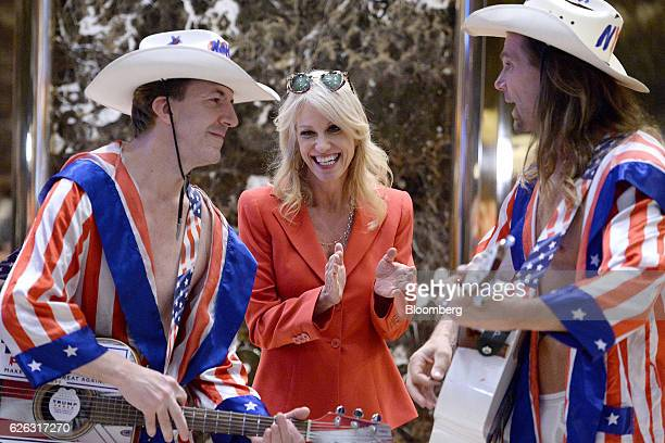Kellyanne Conway senior adviser to US Presidentelect Donald Trump smiles while standing next to 'Naked Cowboy' performers in the lobby at Trump Tower...