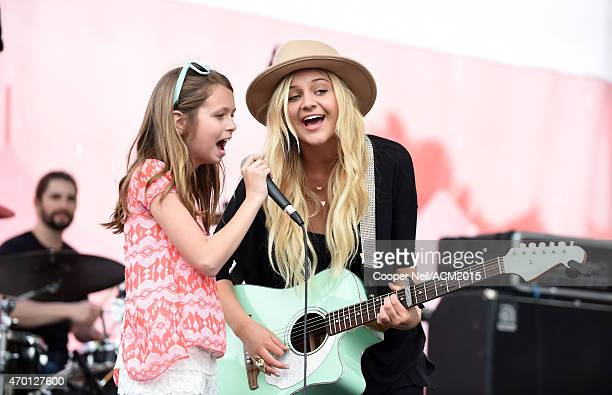 Kelsea Ballerini performs onstage with a fan during the ACM Party For A Cause Festival at Globe Life Park in Arlington on April 17 2015 in Arlington...