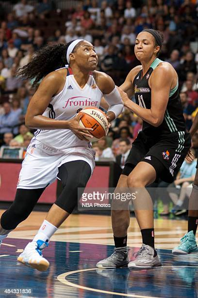 Kelsey Bone of the Connecticut Sun drives to the basket against Kiah Stokes of the New York Liberty on August 14 2015 at the Mohegan Sun Arena in...