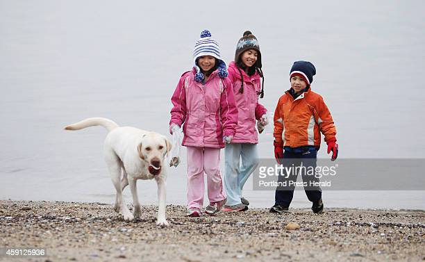 Kelsey Crocker of Cumberland her sister Kylie and their brother Kannon laugh as their dog Lexi carries a tennis ball she found in the water onto East...
