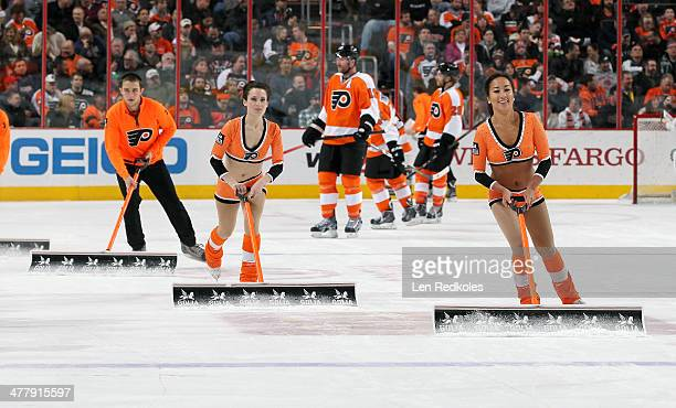 Kelsey Hoffman and Erika Choi Smith of the Philadelphia Flyers ice girls clean the ice during a stoppage in play against the Washington Capitals on...