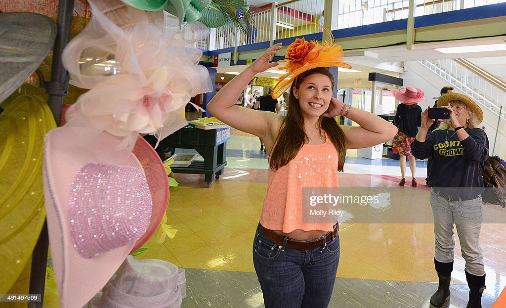 Kelsey Olsen tries on a hat while her mom Jeanne takes a photo during racing at Pimlico Race Course on May 15 2014 in Baltimore Maryland