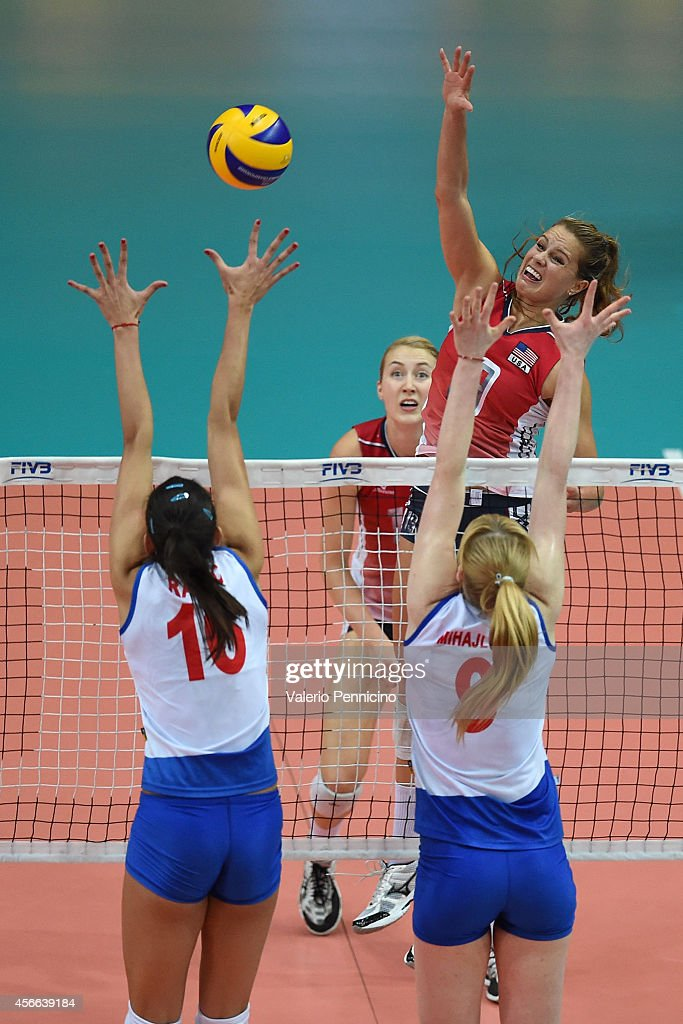 Kelsey Robinson of USA spikes as Brankica Mihajlovic (R) and Milena Rasic (L) of Serbia block during the FIVB Women's World Championship pool F match between Serbia v USA on October 4, 2014 in Verona, Italy.