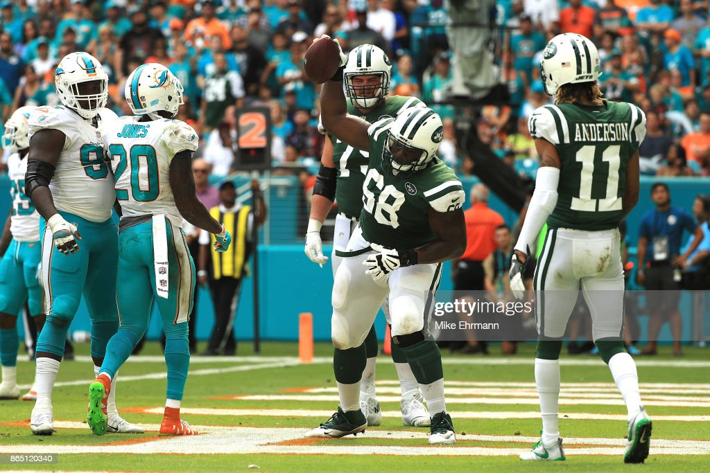 Kelvin Beachum #68 of the New York Jets spikes the football after his team scored a touchdown during the second quarter against the Miami Dolphins at Hard Rock Stadium on October 22, 2017 in Miami Gardens, Florida.