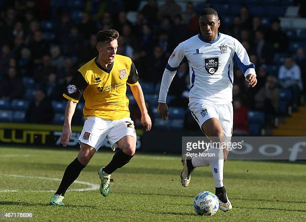 Kelvin Etuhu of Bury looks to play the ball watched by Diego De Girolamo of Northampton Town during the League Two match between Bury and Northampton...
