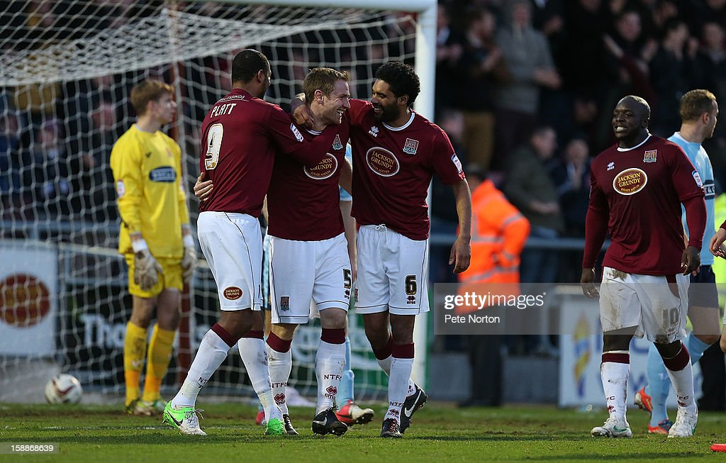 Kelvin Langmead of Northampton Town is congratulated by team mates Clive Platt and Anthony Charles after scoring his sides 3rd goal during the npower League Two match between Northampton Town and Dagenham & Redbridge at Sixfields Stadium on January 1, 2013 in Northampton, England.