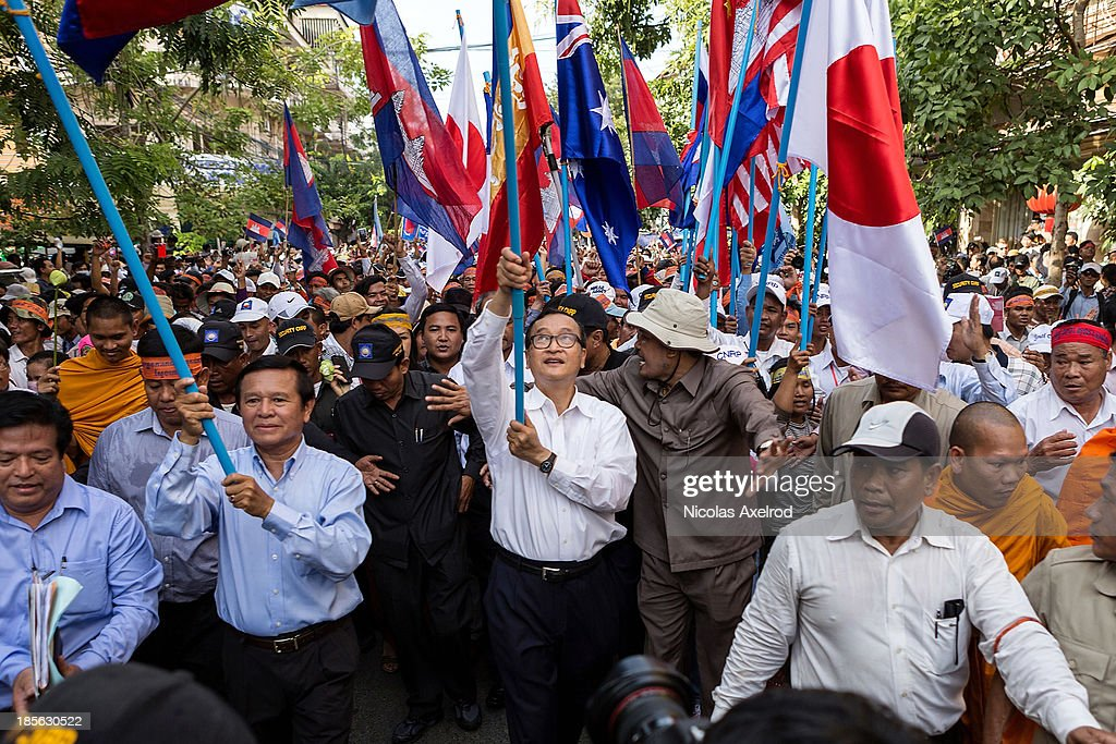 Kem Sokha (L), Vice-President of the CNRP and <a gi-track='captionPersonalityLinkClicked' href=/galleries/search?phrase=Sam+Rainsy&family=editorial&specificpeople=660347 ng-click='$event.stopPropagation()'>Sam Rainsy</a> (C), President of the CNRP hold up flags as they march to the UN offices to deliver a petition on October 23, 2013 in Phnom Penh, Cambodia. The Cambodian National Rescue Party hold the first day of a three day protest in commemoration of the 22nd anniversary of the October 23, 1991 Paris Peace Accords. The CNRP delivered a petition of over 2 million thumbprints to the UN Cambodia Office of the High Commissioner for Human Rights asking for the UN to assist in resolving the current political deadlock caused by a dispute over the country's July elections.