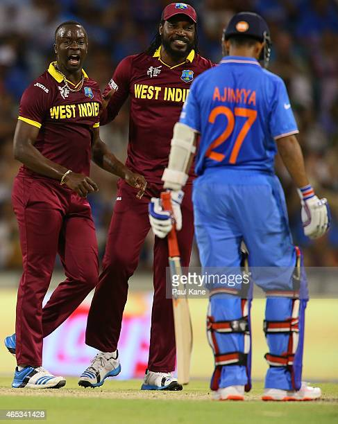 Kemar Roach and Chris Gayle of the West Indies celebrate the wicket of Ajinkya Rahane of India during the 2015 ICC Cricket World Cup match between...