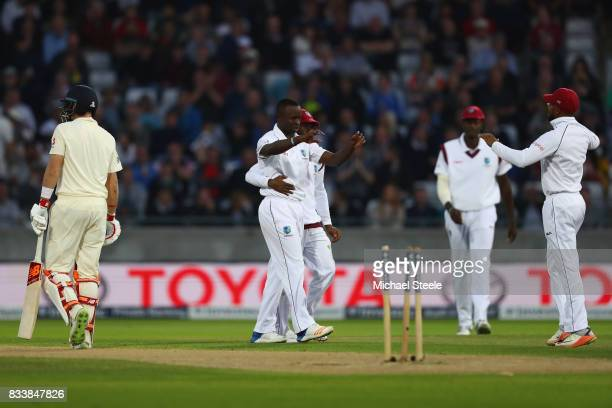 Kemar Roach of West Indies is congratulated by team mates after bowling Joe Root of England during day one of the 1st Investec Test match between...