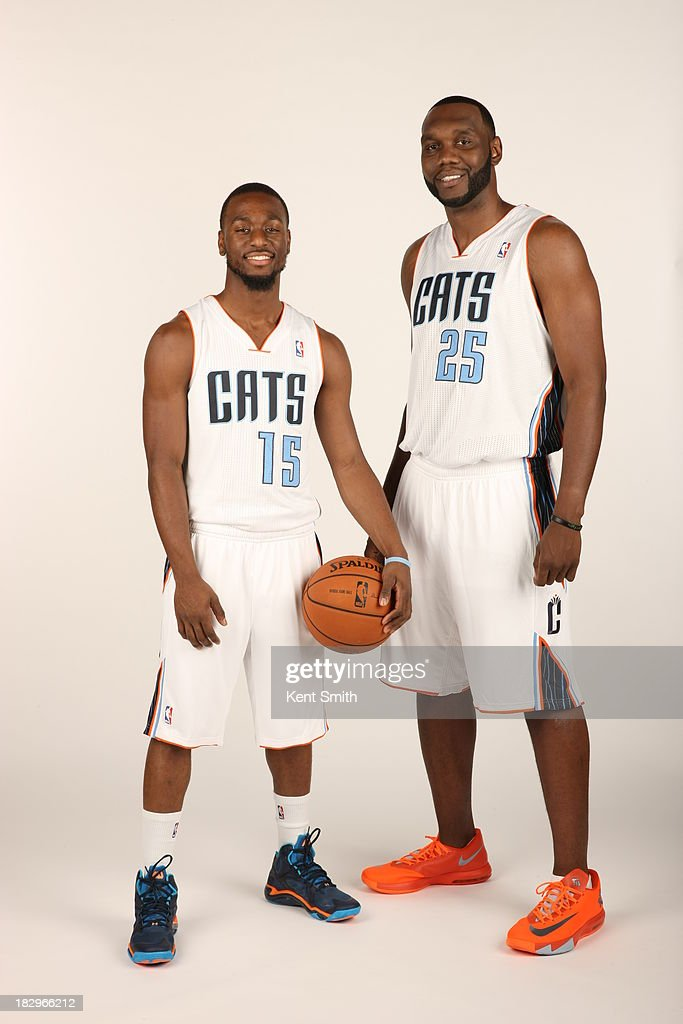 Kemba Walker #15 and Al Jefferson #25 of the Charlotte Bobcats pose for a portrait on media day at the Time Warner Cable Arena on September 30, 2013 in Charlotte, North Carolina.
