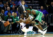 Kemba Walker of the Charlotte Bobcats and Gerald Wallace of the Boston Celtics fight for a loose ball during their game at Time Warner Cable Arena on...