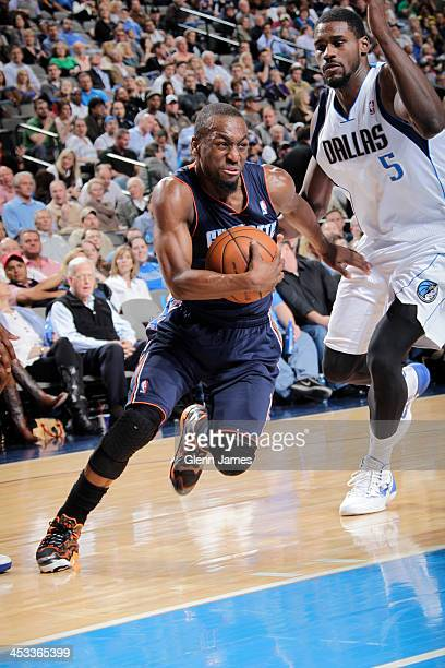 Kemba Walker of the Charlotte Bobcats drives against Bernard James of the Dallas Mavericks on December 3 2013 at the American Airlines Center in...