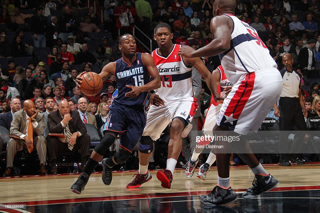 Kemba Walker #15 of the Charlotte Bobcats drives against Kervin Seraphin #13 and Emeka Okafor #50 of the Washington Wizards during the game at the Verizon Center on March 9, 2013 in Washington, DC.