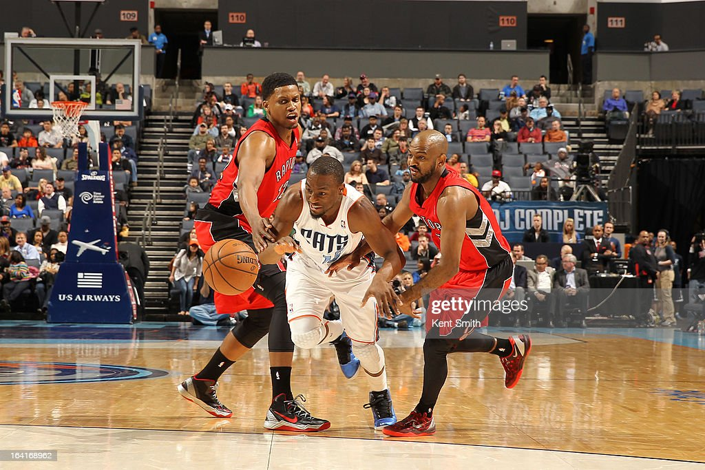 Kemba Walker #15 of the Charlotte Bobcats drives against Rudy Gay #22 and John Lucas III #5 of the Toronto Raptors at the Time Warner Cable Arena on March 20, 2013 in Charlotte, North Carolina.