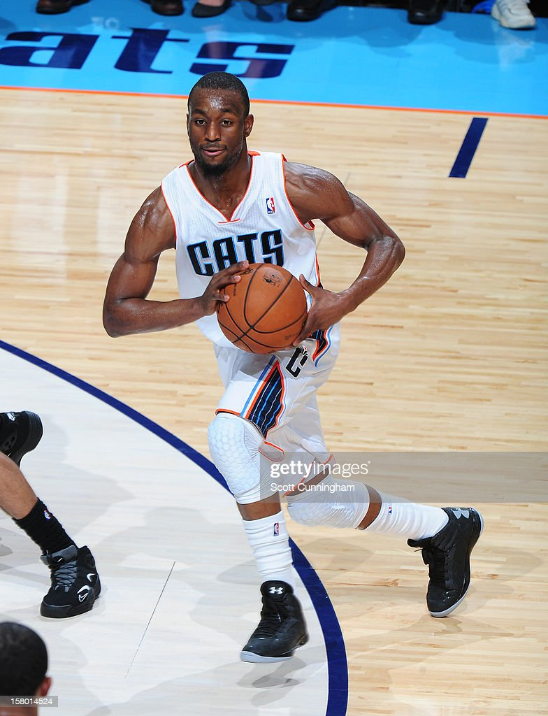Kemba Walker #15 of the Charlotte Bobcats drives to the basket and looks to pass the ball against the San Antonio Spurs at Time Warner Cable Arena on December 8, 2012 in Charlotte, North Carolina.