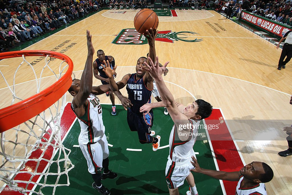 Kemba Walker #15 of the Charlotte Bobcats goes to the basket against (L-R) Samuel Dalembert #21 and Ersan Ilyasova #7 of the Milwaukee Bucks during the game on December 7, 2012 at the BMO Harris Bradley Center in Milwaukee, Wisconsin.